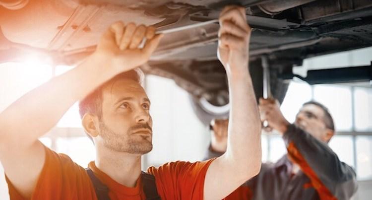 mechanics working under the car hood