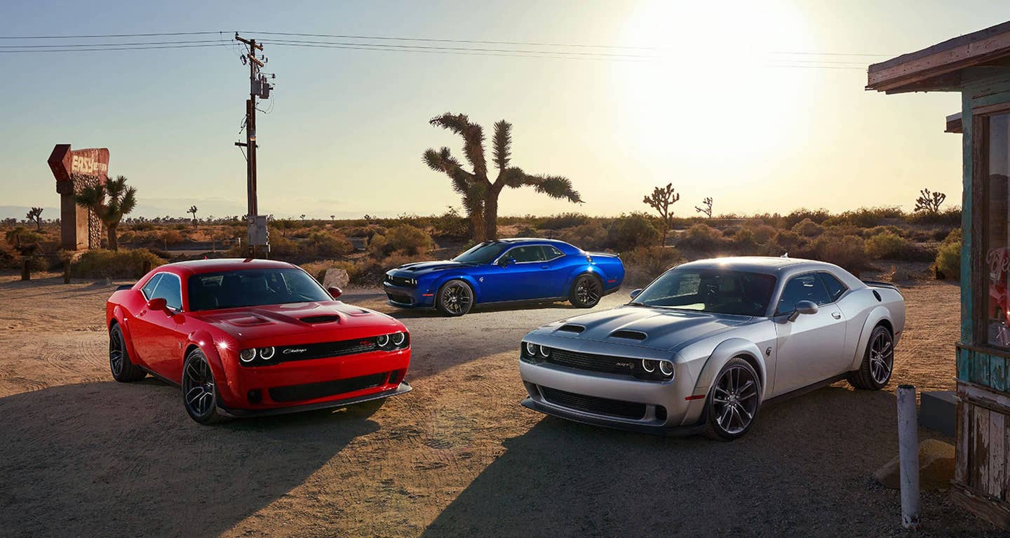 Three 2021 Dodge Challengers parked outside in a desert.