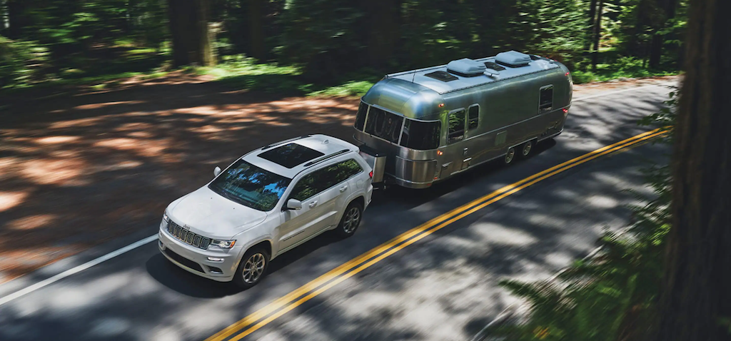 The 2021 Jeep Grand Cherokee towing a trailer in the woods.